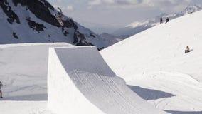 Snowboarderen gör extremt hopp på språngbrädan cameraman solig dag Berg stock video