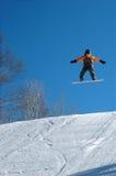 Snowboarderen hoppar high Royaltyfri Bild