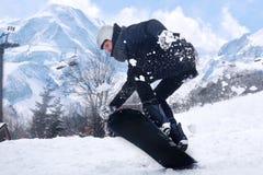 Snowboarderen hoppar med snowboarden från snowhill Landskap för manbanhoppningberg i bakgrund Snowboarderskidåkning i höjdpunkt Royaltyfri Bild