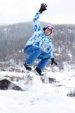 Snowboarderen hoppar på snowboard och vågr förbi handen Arkivfoto