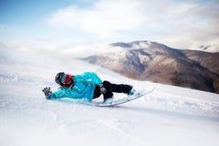 Snowboarderen i höga berg under solig dag lägger på snö royaltyfri bild