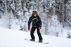 Snowboarderen i svart dräkt glider ner royaltyfria bilder