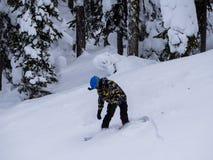 Snowboarderen klibbar landa av av hoppet Royaltyfria Bilder
