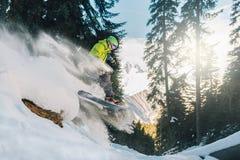 Snowboarderen med special utrustning är rida och hoppa mycket snabbt i bergskogen Royaltyfria Bilder