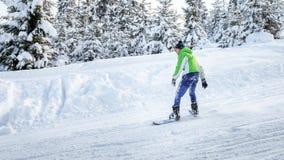 Snowboarderen rider en snowboard på skidalutningen Arkivbild