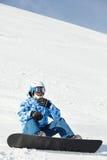 Snowboarderen skidar in dräkten sitter på snöig back Arkivbild