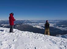 Snowboarderen står för nedstigningen från berget royaltyfria foton