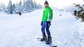 Snowboarderen står på snowboarden i vintern på en skidakörning Royaltyfri Fotografi