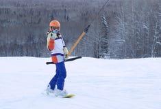 Snowboarderen stiger upp berget på skidlift Arkivfoton