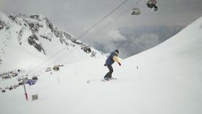 Snowboarderfahrt unten auf Steigung an den schneebedeckten Bergen uniform Ski Lifts Makro des grünen Grases Extreme Liebhaberei stock video footage