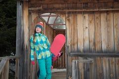 Snowboarderflicka som vilar på terrassen av ett trähus Royaltyfri Foto