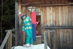 Snowboarderflicka som vilar på terrassen av ett trähus Royaltyfria Foton