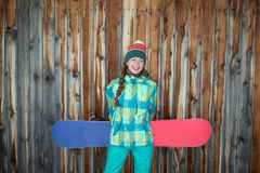 Snowboarderflicka som vilar på terrassen av ett trähus Arkivbilder