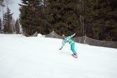 Snowboarderflickaridning på huvudvägen ner från bergen Arkivbilder