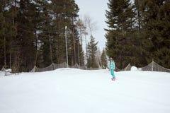 Snowboarderflickaridning på huvudvägen ner från bergen Arkivfoton