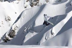 Snowboarderfliegen auf dem Hintergrund der schneebedeckten Steigung Extremer Wintersport, Snowboarding lizenzfreies stockbild