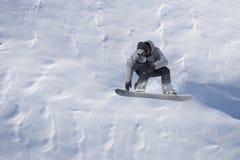 Snowboarderfliegen auf dem Hintergrund der schneebedeckten Steigung Extremer Wintersport, Snowboarding stockfotografie