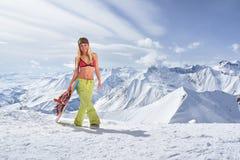 Snowboardermädchen in einem Badeanzug gehend auf Berg Lizenzfreie Stockfotos