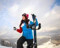 Snowboardermädchen im Winter gelangen Reichweite an die Spitze des Berges Lizenzfreie Stockfotos