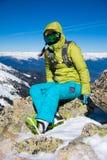 Snowboardermädchensitzen Stockfoto