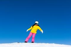 Snowboardermädchen, das Bremsungstrick auf Snowboard macht Lizenzfreie Stockfotos