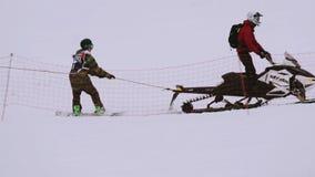 Snowboarderrit op sneeuwscooterholding op kabel Het van brandstof voorzien van de benzinepomp Bergen Sport stock videobeelden