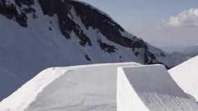 Snowboarderrit op springplank Maak volledige tik in lucht Zonnige dag Bergen stock videobeelden
