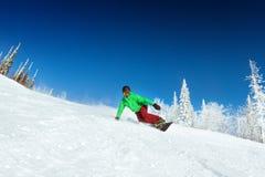 Snowboarderritten bij helling het snowboarding stock fotografie