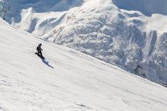 Snowboarderritter på ett brant skidar lutningen på en solig vinterdag fotografering för bildbyråer