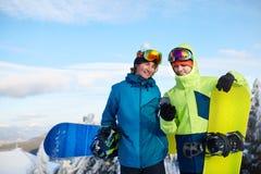 2 snowboarders говоря и держа смартфоны Друзья смотря мобильный телефон и связывая в социальной сети стоковое изображение rf