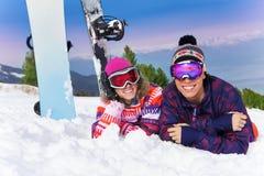 2 snowboarders лежа совместно на снеге Стоковая Фотография