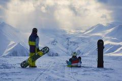 Snowboarders имеют остатки и взгляд на ландшафте гор зимы Стоковое Изображение