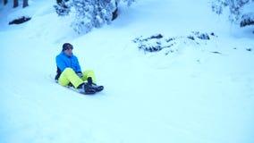 Snowboarders имеют потеху на сноубордах около домов в древесинах видеоматериал
