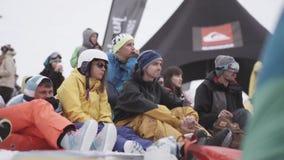 Snowboarders и лыжники на событии внутри располагаются лыжа курорта смелости Спортивное мероприятие видеоматериал