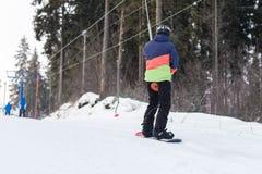 Snowboarders и лыжники поднимают на подъем вверх Стоковое Изображение