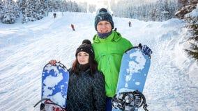 Snowboarders пар стоя на наклоне лыжи Стоковое Фото