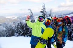 3 snowboarders принимая selfie с камерой смартфона на лыжный курорт Друзья фотографируя для социальной публикации сети стоковое фото rf