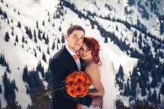 Snowboarders свадьбы соединяют как раз пожененный на зиме горы Стоковые Изображения