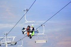 3 snowboarders сидя на ropeway Стоковая Фотография