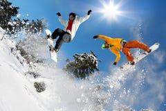 Snowboarders скача против голубого неба Стоковая Фотография
