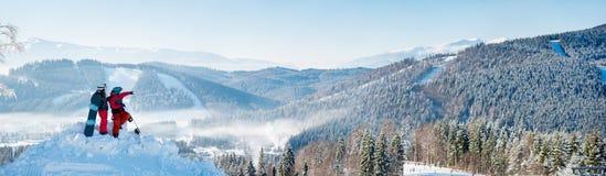 Snowboarders соединяют положение na górze горы стоковое изображение