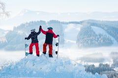 Snowboarders соединяют положение na górze горы стоковое фото rf