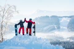Snowboarders соединяют положение na górze горы Стоковые Изображения