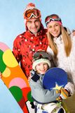 Snowboarders. Portrait of happy family with snowboards looking at camera on blue background Stock Photo