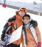 Snowboarders afortunados de los pares en un valle de la montaña Foto de archivo libre de regalías
