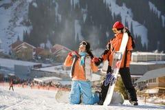 Snowboarders chanceux de couples dans une vallée Images stock