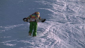 Snowboarders climbing to mountain top stock video