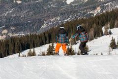 Snowboarders con el casco en snowpark, gemelos del estilo libre Imagen de archivo