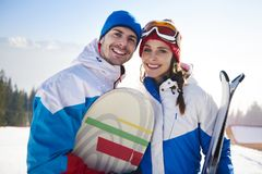 Couple with snowboards and skis Royalty Free Stock Photography
