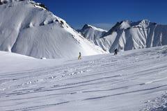 Snowboarders cuesta abajo en de cuesta del piste con nieve nuevo-caida Foto de archivo libre de regalías